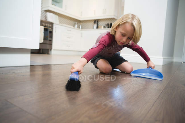 Boy sweeping dust with brush and dust pan at home — Stock Photo