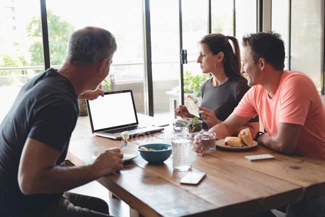 Compañeros de negocios discutiendo sobre el ordenador portátil mientras desayunan en la oficina - foto de stock