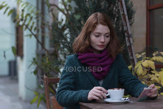 Женщина с помощью мобильного телефона имея капучино в кафе на открытом воздухе — стоковое фото