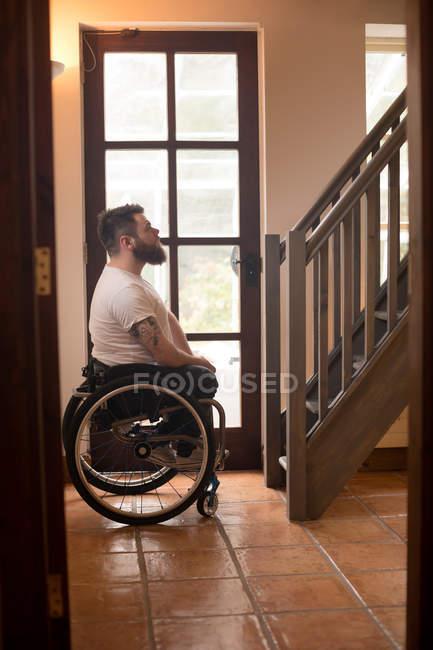 Vista lateral do homem com deficiência em cadeira de rodas olhando escadas — Fotografia de Stock
