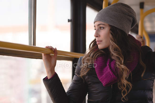 Young woman looking through window while travelling in train — Stock Photo