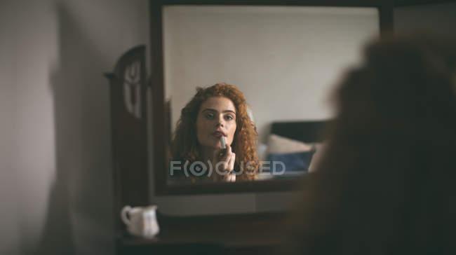 Женщина применения помады перед зеркалом дома — стоковое фото