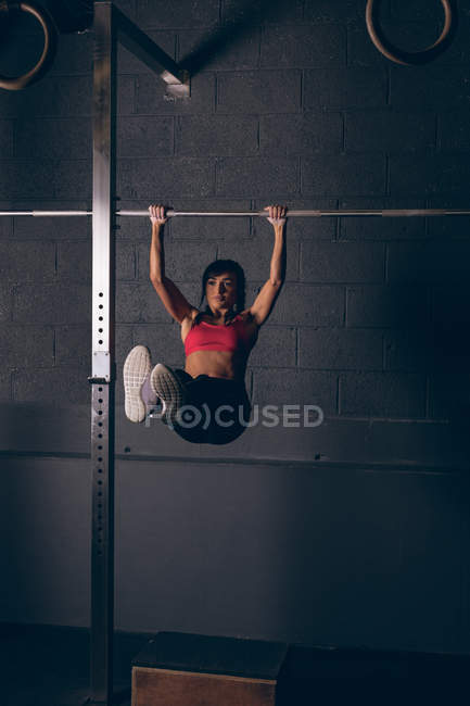 Fit woman exercising on a bar in the gym — Stock Photo
