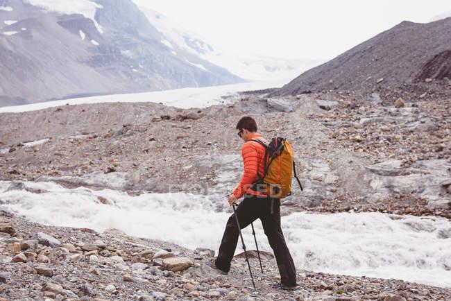 Randonneur mâle avec sac à dos marchant près de la rivière sur une journée ensoleillée — Photo de stock