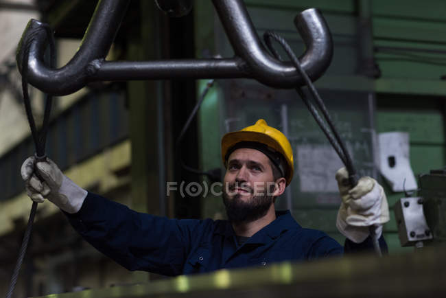 Attentive technician adjusting metal equipment in hook — Stock Photo
