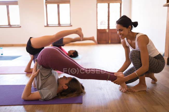 Trainerin unterstützt Frau bei Yoga-Übungen im Fitnessclub — Stockfoto