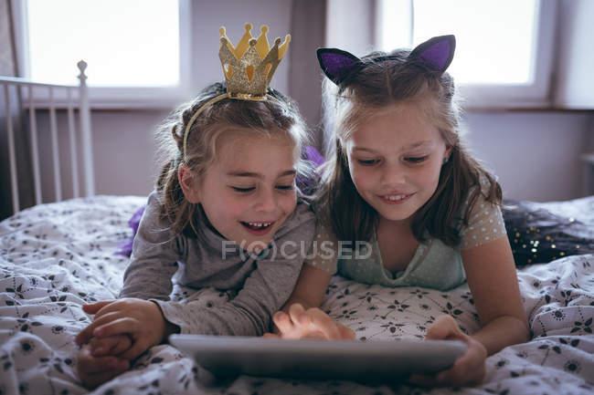Sœurs utilisant tablette numérique sur le lit à la maison — Photo de stock