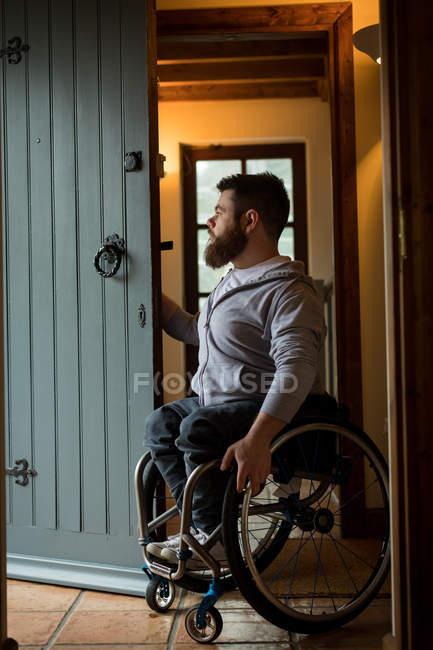 Hombre discapacitado cerrando la puerta de su casa - foto de stock