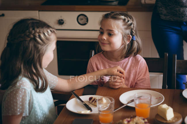 Sisters interacting with each other while having breakfast in kitchen — Stock Photo