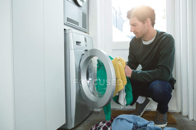 Man putting clothes in washing machine at home — Stock Photo