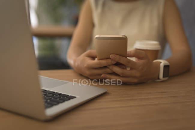 Donna d'affari che utilizza il telefono cellulare alla scrivania in ufficio — Foto stock
