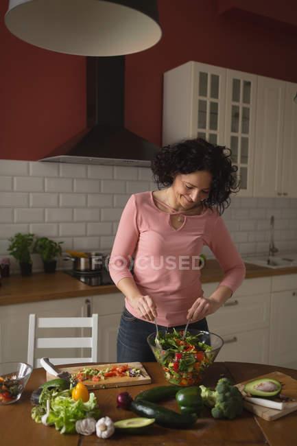 Femme préparant la salade de légumes dans la cuisine à la maison — Photo de stock