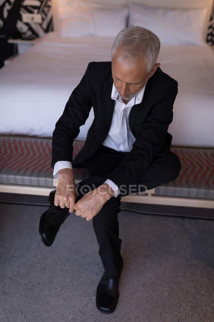 Homme d'affaires liant son lacet dans la chambre d'hôtel — Photo de stock