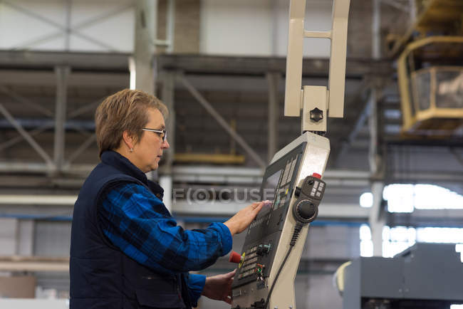 Female technician operating machine in metal industry — Stock Photo