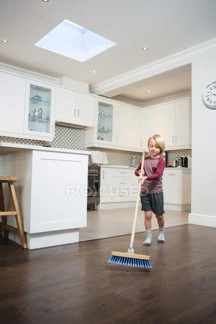 Хлопчик очищення підлога з мітлою кухні в домашніх умовах — стокове фото