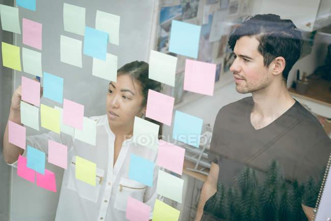 Керівників бізнесу, обговорюючи над наліпок в офісі — стокове фото
