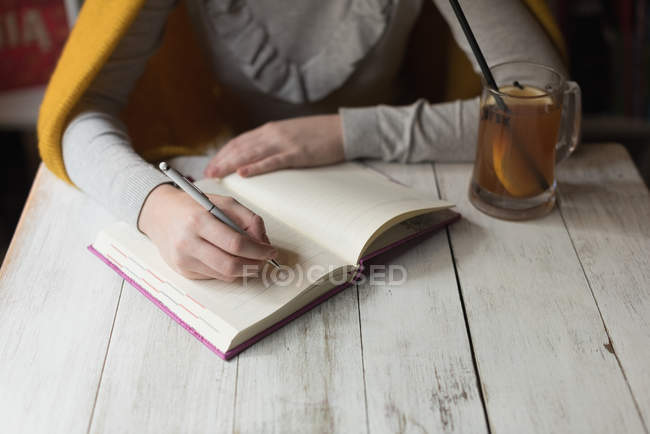 Mid section of woman writing note on book with lemon juice on table — Stock Photo