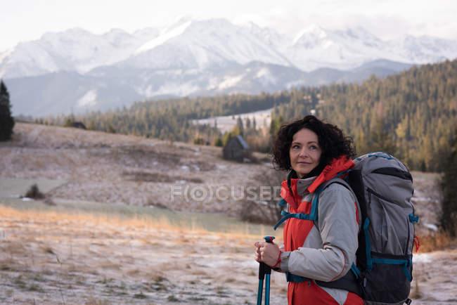 Donna premurosa in piedi con zaino e palo da trekking durante l'inverno — Foto stock