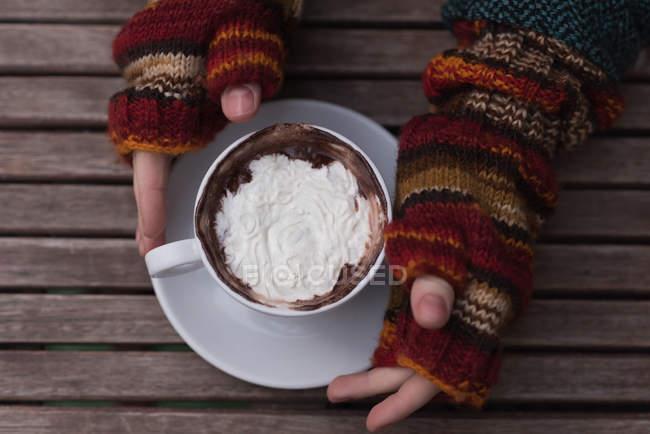 Накладные расходы женщины, пьющей капучино в кафе на открытом воздухе — стоковое фото