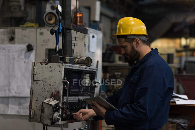 Attentive technician checking machine in metal industry — Stock Photo