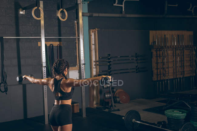 Fit woman exercising with dumbbells in the gym — Stock Photo