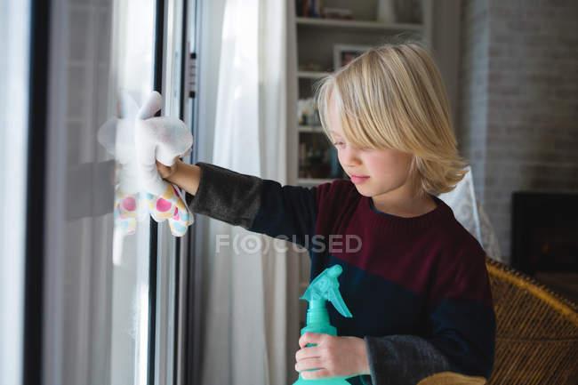 Janela de limpeza menino com pano de pano em casa — Fotografia de Stock