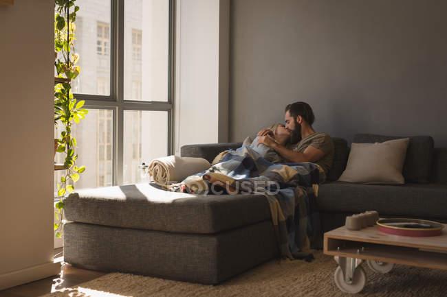 Coppia baciarsi in soggiorno a casa — Foto stock