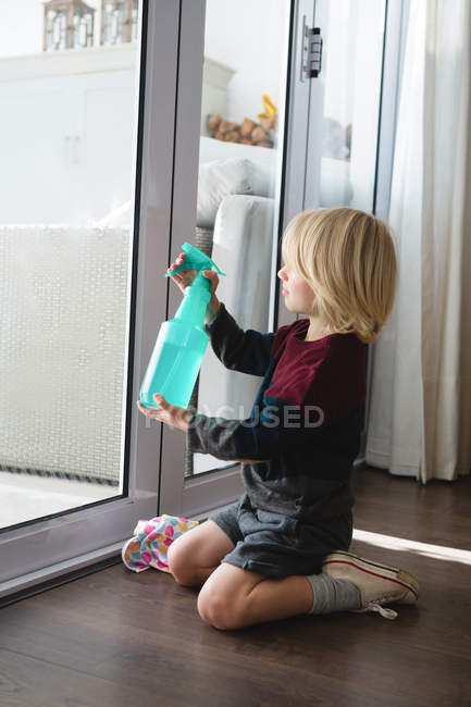 Boy cleaning window with rag cloth at home — Stock Photo