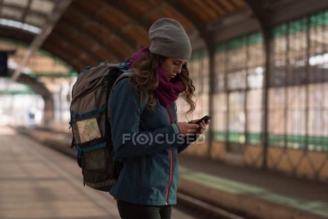 Jovem usando telefone celular na estação ferroviária — Fotografia de Stock