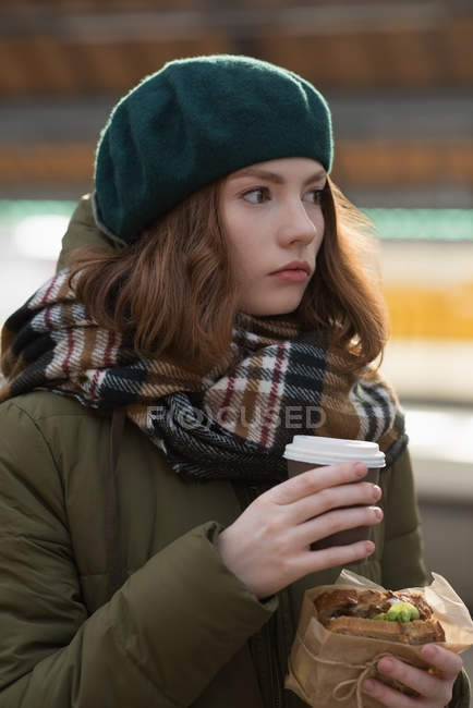 Женщина в зимней одежде с оберткой и кофе на вокзале — стоковое фото