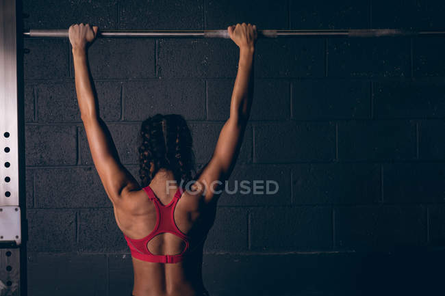 Rear view of fit woman exercising on a bar in the gym — Stock Photo