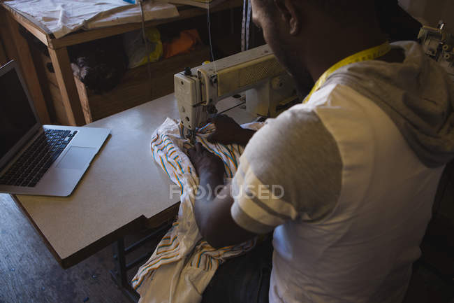 Tailor sewing clothes on sewing machine in shop — Stock Photo