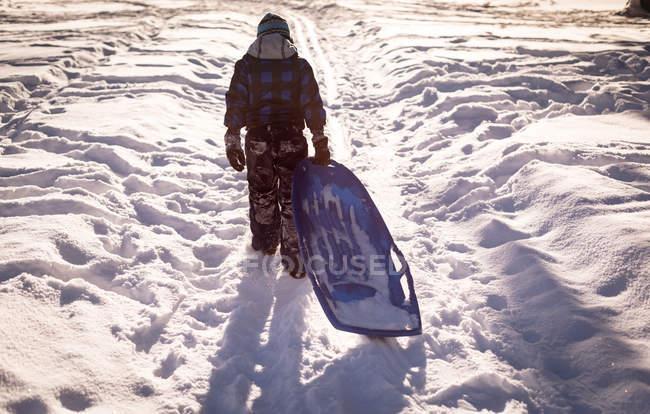Vista posterior de chica caminando con trineo en la nieve durante el invierno - foto de stock