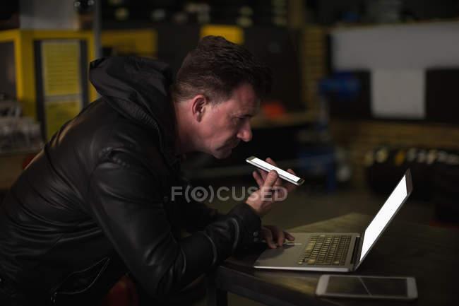 Механік говорити на мобільному телефоні під час використання ноутбука в гаражі — стокове фото