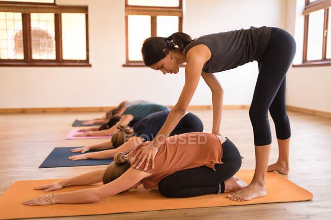 Женщина-тренер помогает женщине в занятиях йогой в фитнес-клубе — стоковое фото