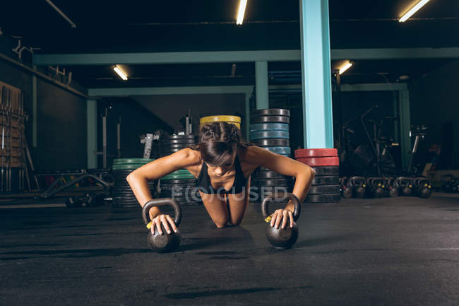 Fit woman exercising with kettlebell in the gym — Stock Photo