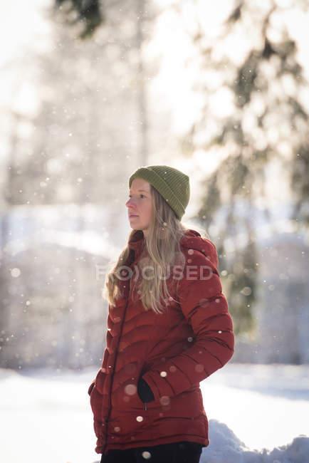 Mujer reflexiva permanente sobre el paisaje cubierto de nieve durante el invierno - foto de stock