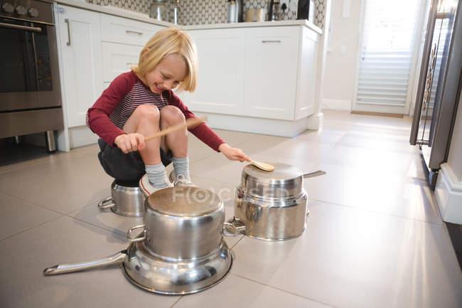Garçon jouer avec des ustensiles dans la cuisine à la maison — Photo de stock