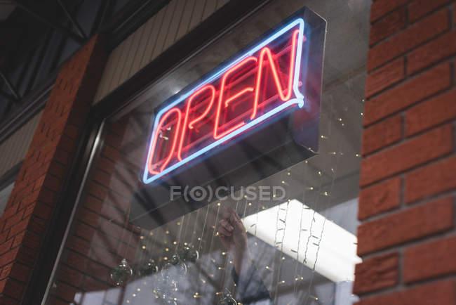 Primer plano de la tienda con cartel abierto con luz de neón - foto de stock