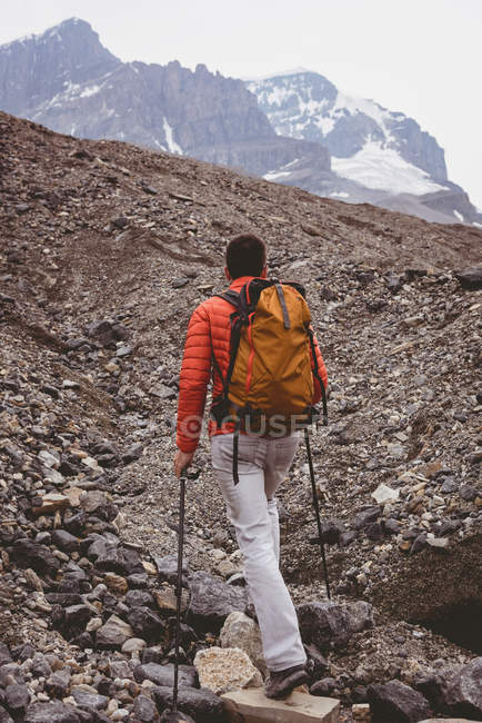 Vista traseira do alpinista masculina com mochila andando na montanha — Fotografia de Stock