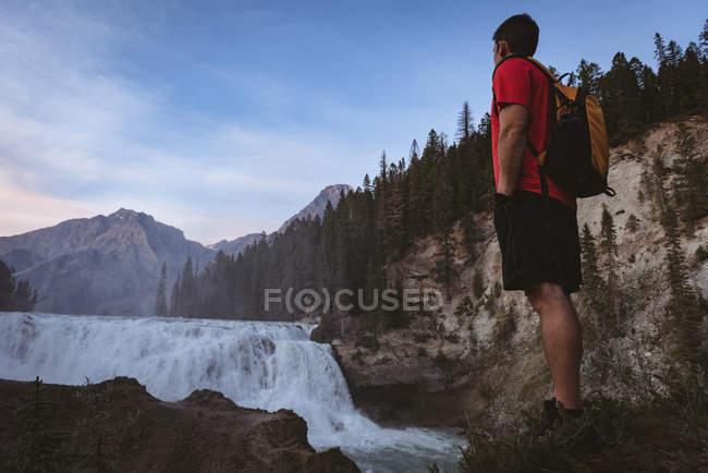 Homme avec sac à dos se tenant près cascade — Photo de stock