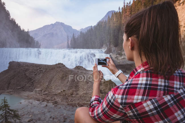 Rear view of woman taking photo of waterfall with mobile phone — Stock Photo
