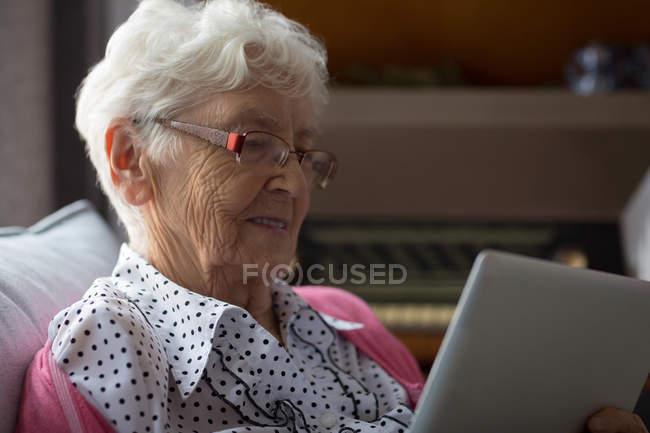 Старшие женщины на дому с использованием цифрового планшета — стоковое фото