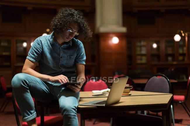 Jovem usando tablet digital na biblioteca — Fotografia de Stock