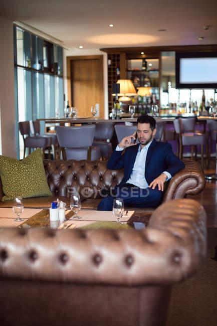 Empresario hablando por teléfono móvil en hotel - foto de stock