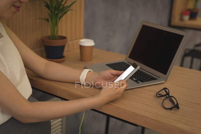 Femme d'affaires enceinte utilisant un téléphone portable au bureau — Photo de stock