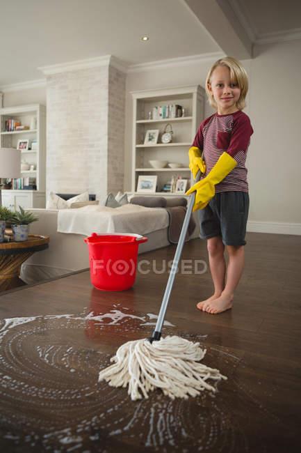 Garçon laver le sol avec de la serpillière à la maison — Photo de stock