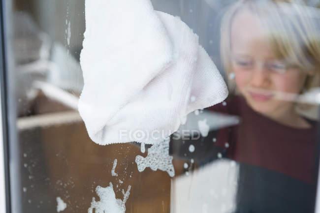 Junge putzt Fenster zu Hause mit Lappen — Stockfoto
