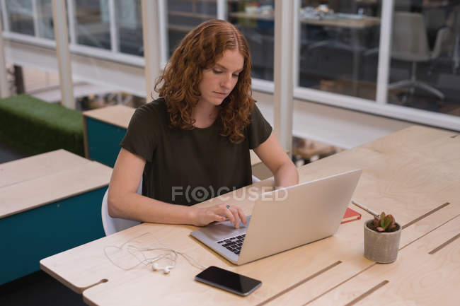 Female executive working at desk in office — Stock Photo