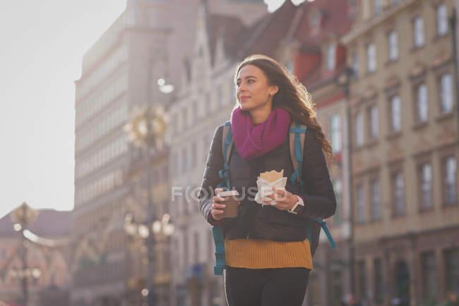 Молодая женщина держит кофе и завтрак на улице — стоковое фото